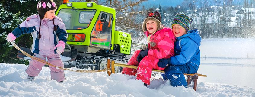 Drei Kinder mit Schlitten auf verschneitem Hügel in Kiefersfelden