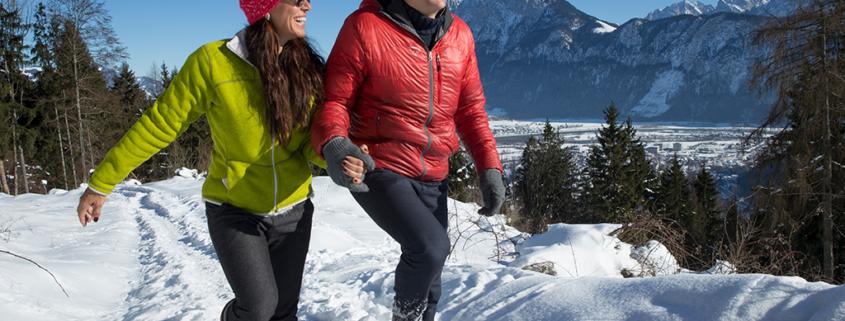 Paar beim Winterwandern in verschneiter Landschaft in Kiefersfelden